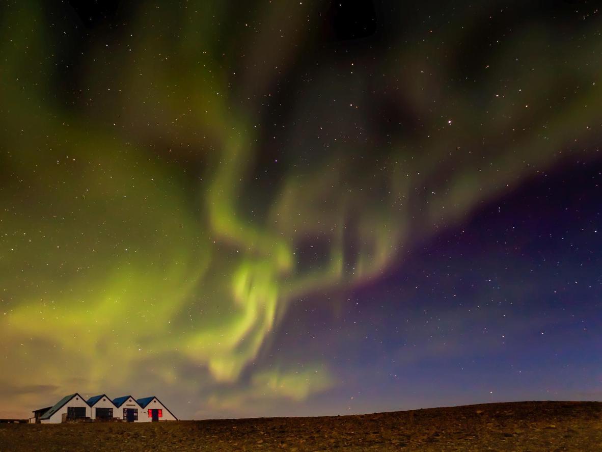 Observe as faixas da Aurora Boreal pelo céu do pequeno vilarejo de Kalfafell