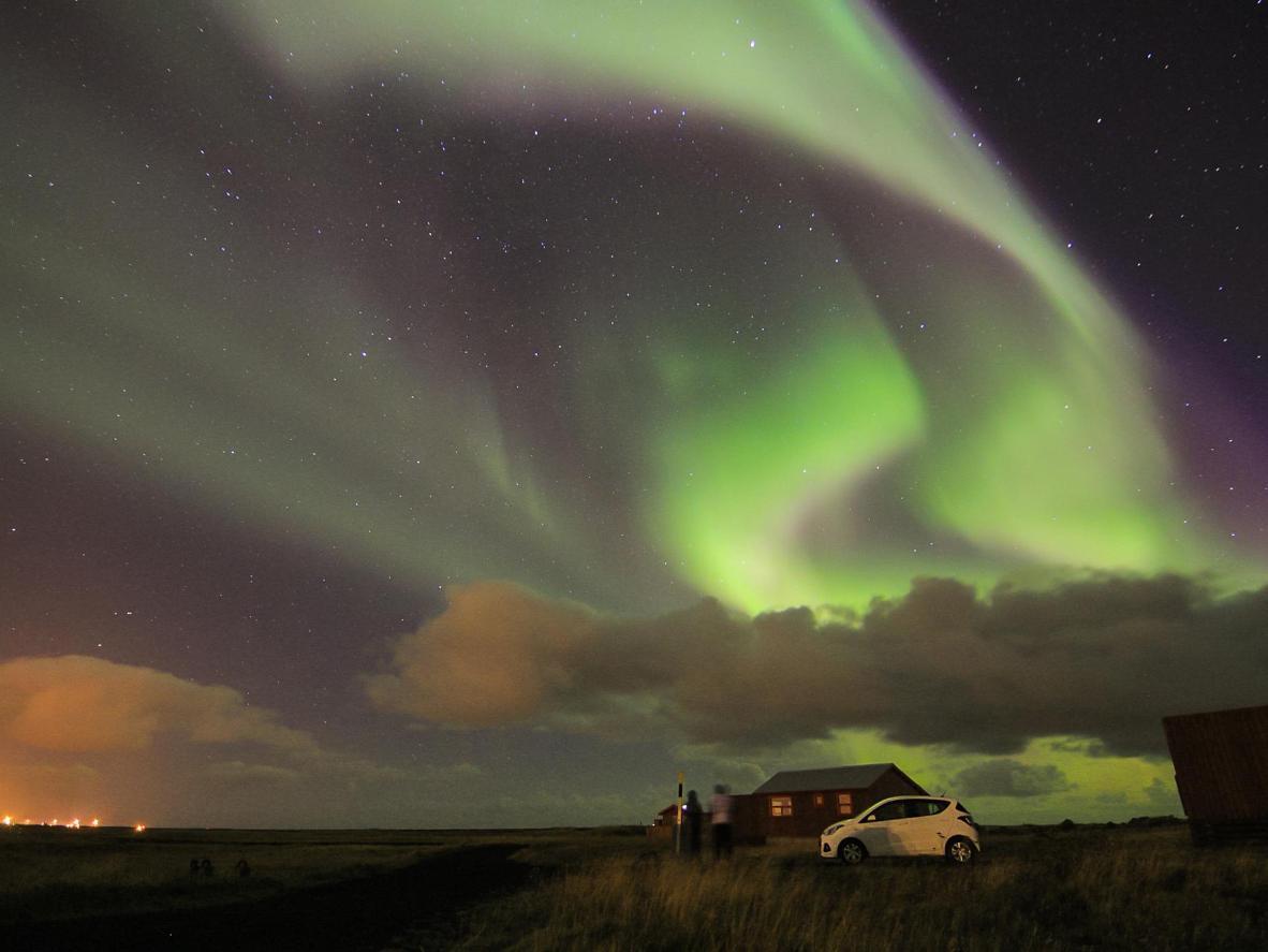 A Aurora Boreal sobre a vila de pescadores de Sandgerdi, Islândia