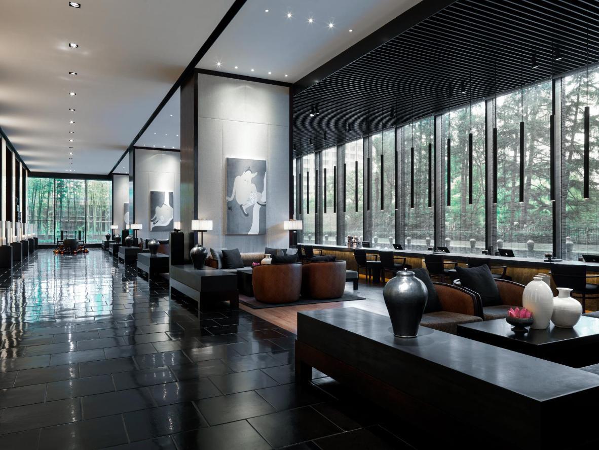 Luz baixa e minimalismo com madeira escura no The Puli Hotel & Spa