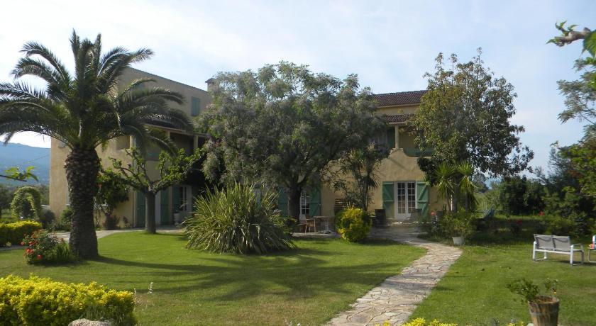 Vue de la façade de l'hôtel, avec jardin ensoleillé