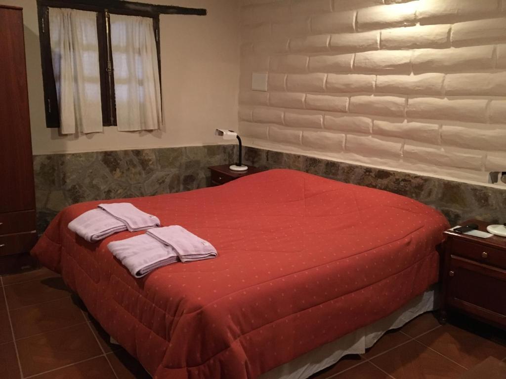 Una cama o camas en una habitación de Hosteria Las Tinajas