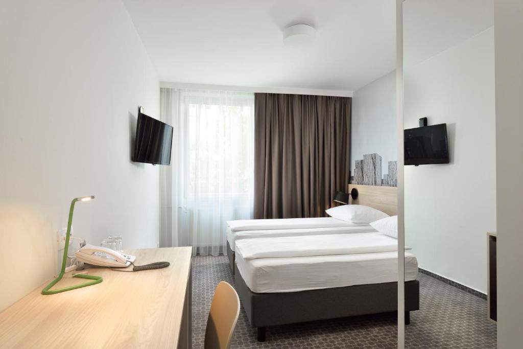 מיטה או מיטות בחדר ב-B&B Hotel Ljubljana Park
