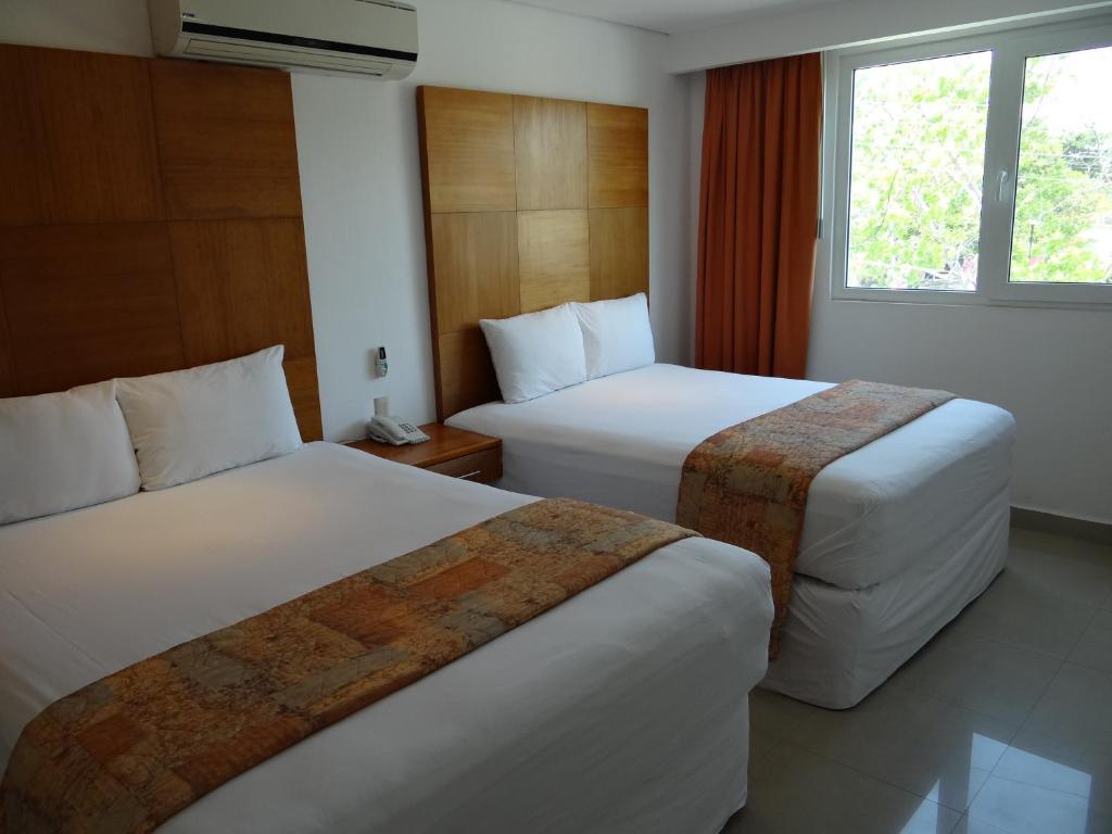 Cama ou camas em um quarto em Hotel Suites Gaby