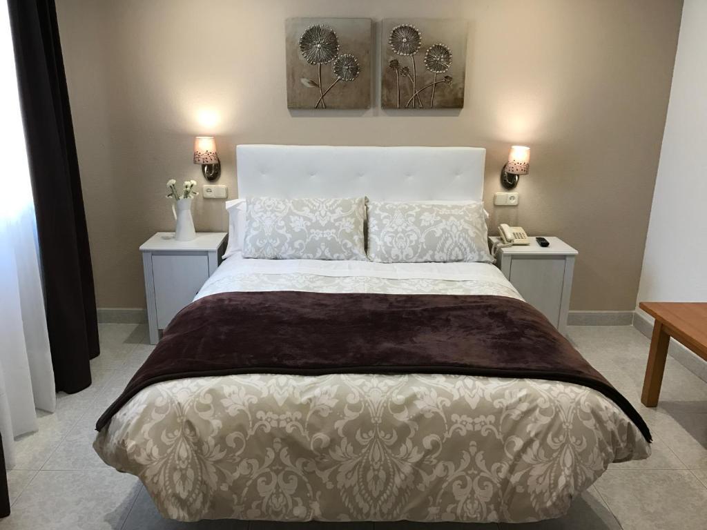 سرير أو أسرّة في غرفة في Hostal Alcázar